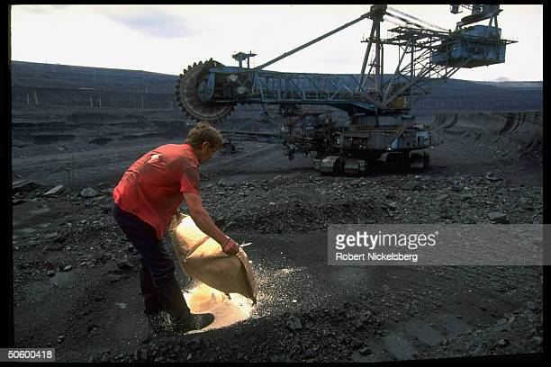 Open pit coal mine workers spreading sacks of granular substance on marked circles in Central Steppes region Ekibastuz