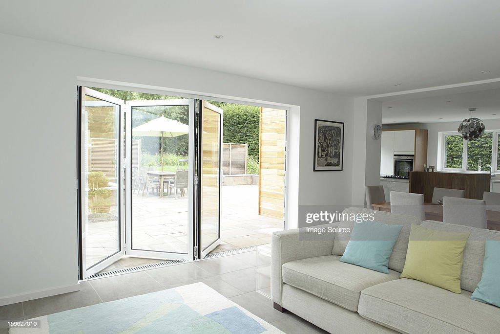 Open plan living area with open patio doors : Stock Photo