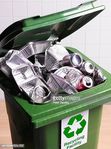 Open recycling bin with full of tin cans and foils, close-up