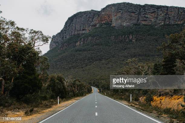 open road against the grampians mountains - victoria australia stock pictures, royalty-free photos & images