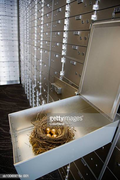 Open safety deposit box with nest and gold eggs inside