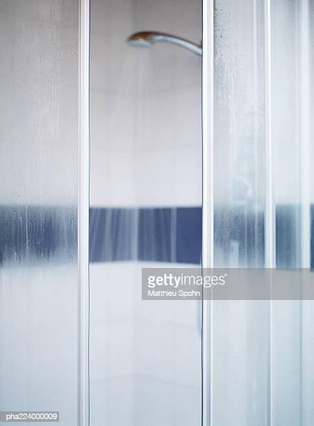 Open shower doors, water running, blurred.