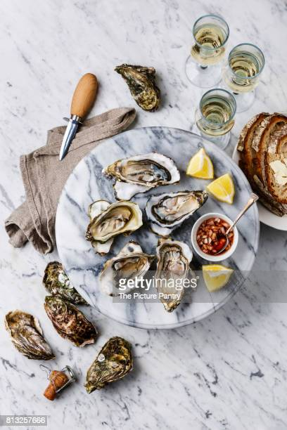 Open shucked Oysters with lemon, bread, butter and champagne on white marble background