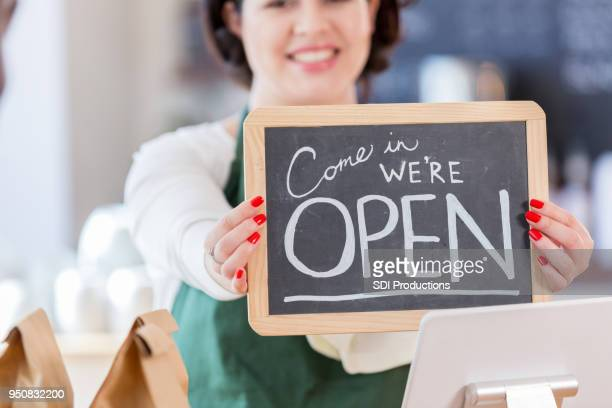 Open sign held by cheerful coffee shop employee
