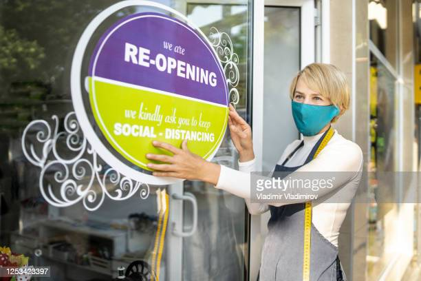 covid-19. open sign in a small business shop after coronavirus pandemic - reopening stock pictures, royalty-free photos & images