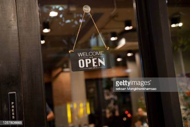 open sign on cafe hang on door at entrance. - building entrance stock pictures, royalty-free photos & images