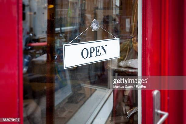 open sign seen through glass door at store - cartello chiuso foto e immagini stock