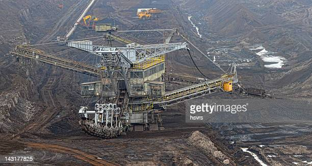 open strip coal mine with bucket-wheel excavator at conveyor belt - coal mining stock photos and pictures
