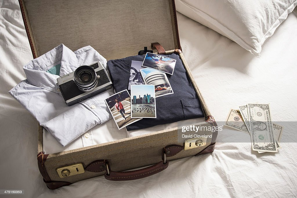 Open suitcase on bed with camera and photographs : Stock Photo