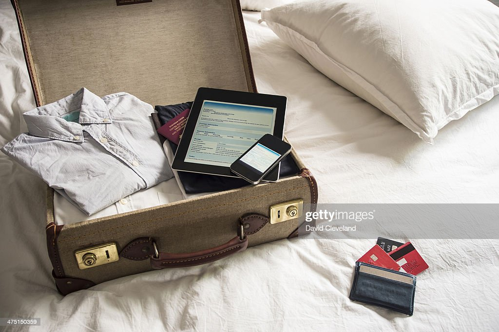 Open suitcase on bed with digital tablet and mobile phone : Foto stock