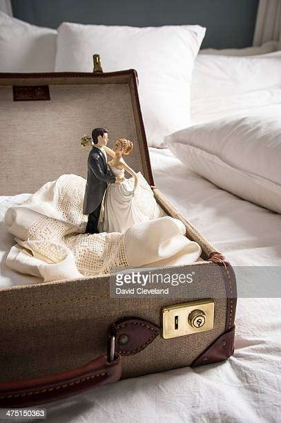 Open suitcase on bed with wedding figurines