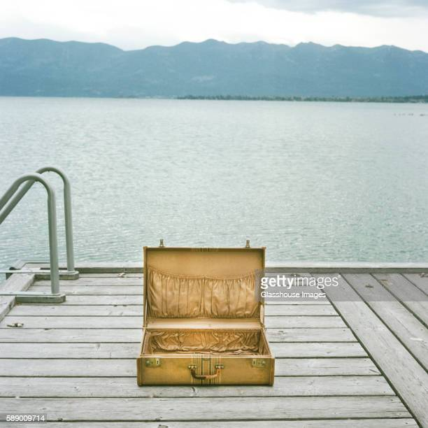 Open Suitcase on Dock with Lake in Background