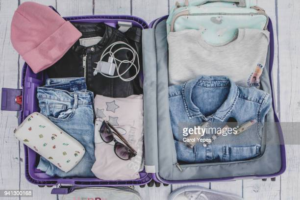 Open suitcase with casual female clothes