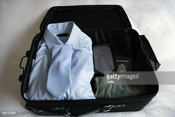 Open suitcase with clothing and passport