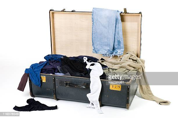 Open suitcase with messy clothes on white background