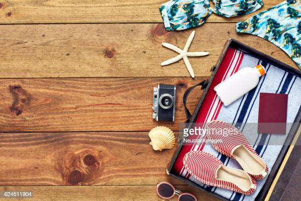 Open suitcase with summer vacation equipment flat lay on wood