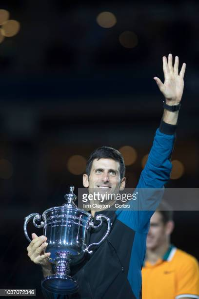 Open Tennis Tournament Day Fourteen Novak Djokovic of Serbia celebrates with the winners trophy watched by runnerup Juan Martin Del Potro of...