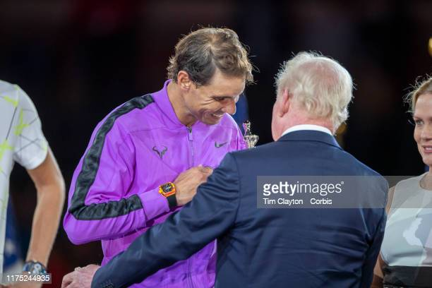 Open Tennis Tournament Day Fourteen Rafael Nadal of Spain is presented with the winner trophy by tennis legend Rod Laver after his victory against...