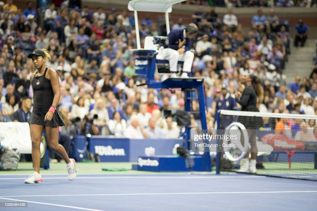 Open Tennis Tournament- Day Thirteen. Chair umpire Carlos Ramos tells Serena Williams of the United States she has received a one game penalty as Naomi Osaka of Japan walks back to the baseline in the Women's Singles Final on Arthur Ashe Stadium at the 2018 US Open Tennis Tournament at the USTA Billie Jean King National Tennis Center on September 8th, 2018 in Flushing, Queens, New York City.
