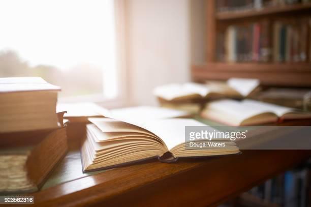 Open vintage books on library desk beside window.