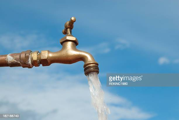 open water faucet against a blue sky - spring flowing water stock pictures, royalty-free photos & images