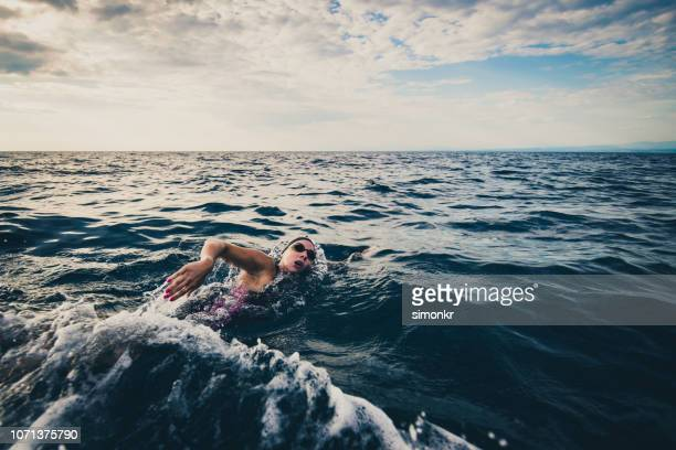 open water swimmer swimming in sea - endurance stock pictures, royalty-free photos & images