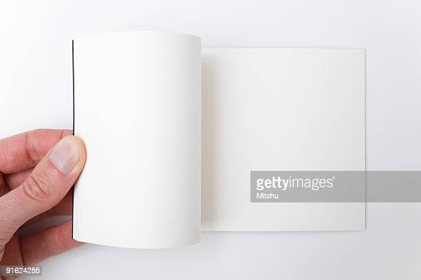 Open white book - A hand flipping pages.
