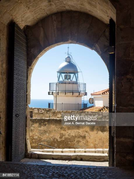 Open wooden doors of a medieval castle, from where you can see an old lighthouse, in the city of Peñiscola, Costa Blanca, Castellon, Spain