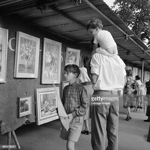 Openair art exhibition Hampstead Greater London 19601965 A boy holding a model yacht and a man with a small child on his shoulders looking at...