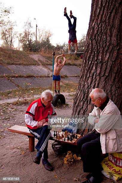 CONTENT] Openair gym frequenters playing chess and exercising on the horizontal bar in Hydropark in Kiev Ukraine