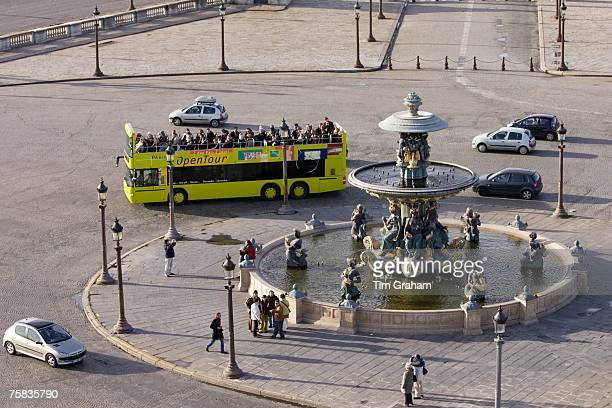 Openair tour bus with tourists passes fountain in Place de la Concorde Central Paris France