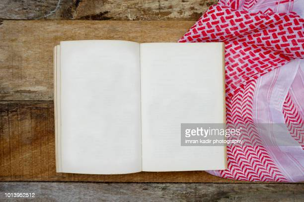 Opened blank book on wooden table with Arabic scarf
