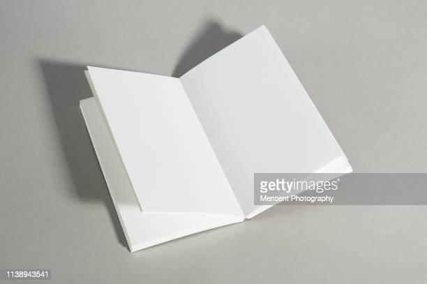 opened blank magazine book on gray background - magazine page stock photos and pictures