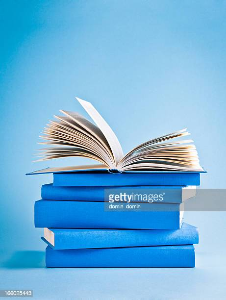 opened book on top of stack of blue books, knowledge - boek stockfoto's en -beelden