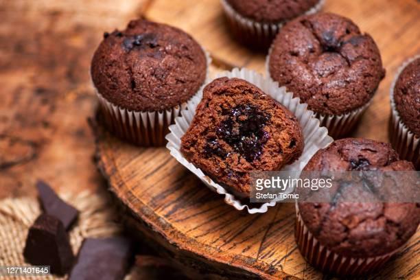 チョコレートクリーム入り紙カップケーキにチョコレートマフィンを開封 - チョコレートチップマフィン ストックフォトと画像