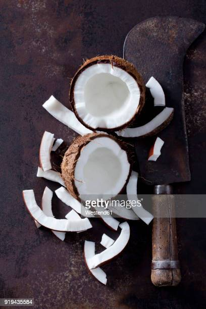 Opened coconut, cocontu pieces and an old cleaver