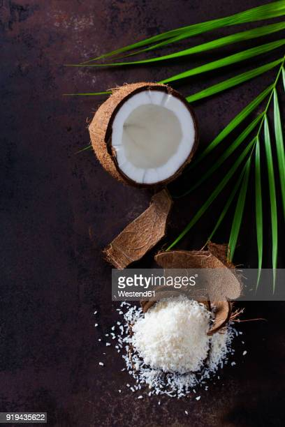 Opened coconut, coconut husk and pile of coconut flakes