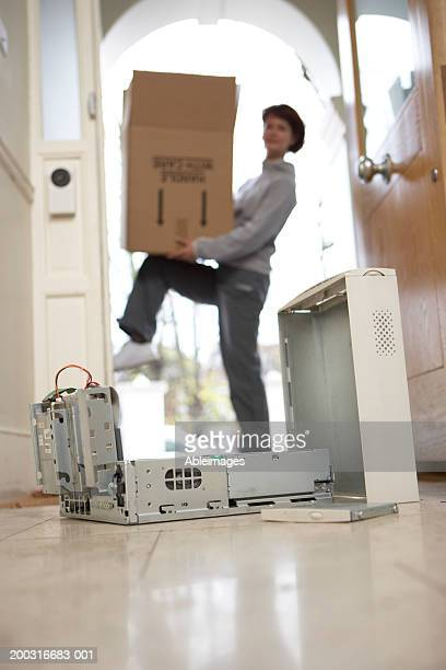 Opened hard drive of computer with woman carrying box in background