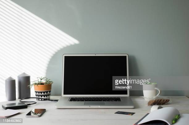 opened laptop on an office desk - bureau stockfoto's en -beelden