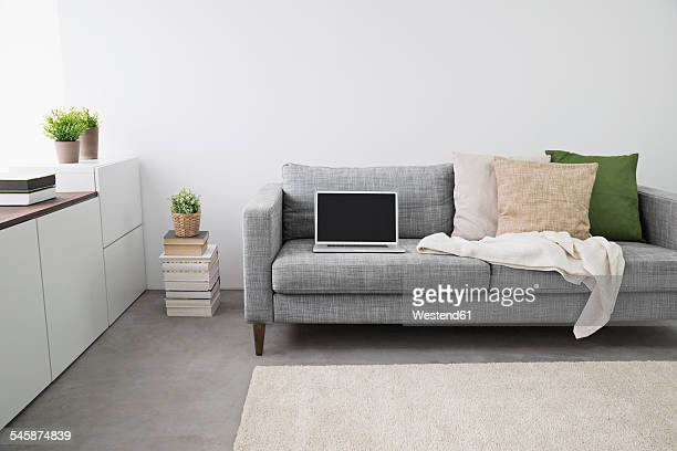 Opened laptop on couch at modern living room