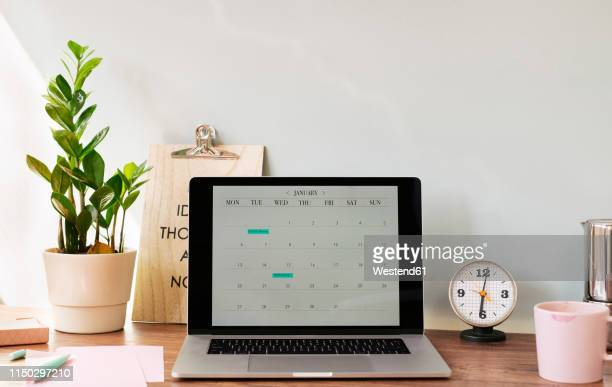 opened laptop with a calendar on desk at home office - bureau stockfoto's en -beelden