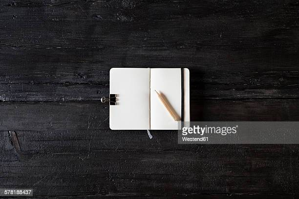 Opened note book and pencil on black wood