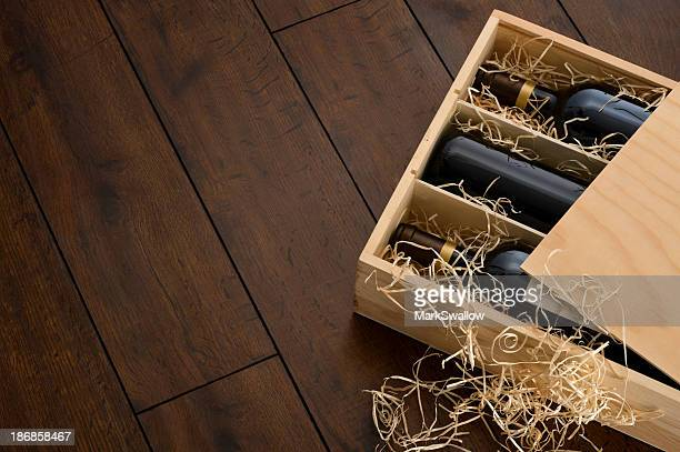 Opened wooden wine box packed with wine and straw