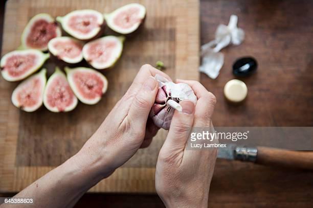 opening a garlic bulb - cabeza de ajos fotografías e imágenes de stock