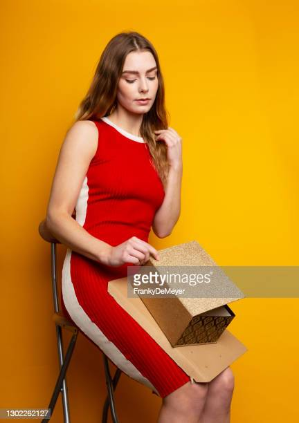 opening a package box, an attractive blonde young woman sits on a chair against yellow background with copy space - mini dress stock pictures, royalty-free photos & images
