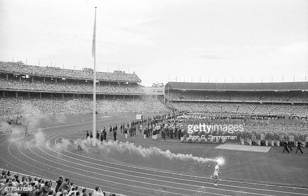1956 Summer Olympics Wide view of Australia Ron Clarke with Olympic torch at Melbourne Cricket Ground Stadium Melbourne Australia CREDIT John G...