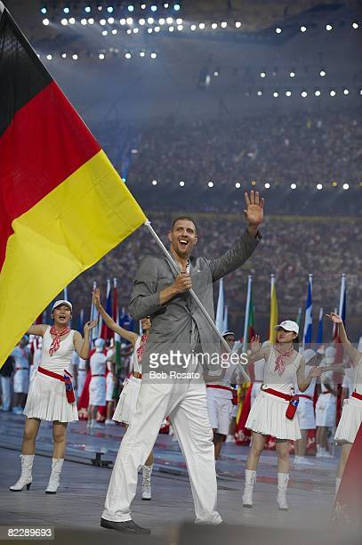 2008 Summer Olympics Team Germany national flag bearer Dirk Nowitzki with delegation during athlete procession at National Stadium Beijing China...