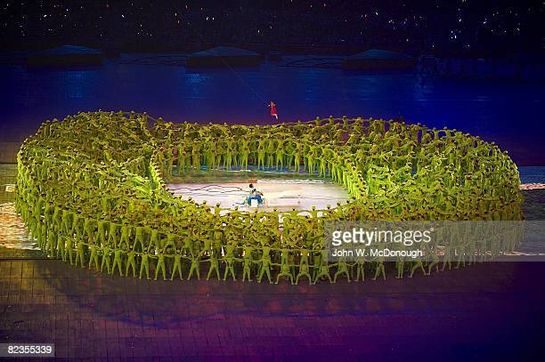 Summer Olympics: View of Chinese pianist Lang Lang and 5-year-old Li Muzi perform in center of human created representation of Bird's Nest stadium at...