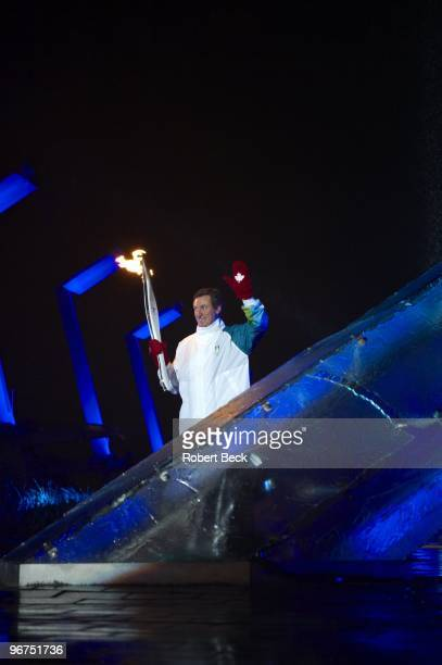 Winter Olympics: View of Canada men's national ice hockey team special advisor Wayne Gretzky holding torch and lighting the outdoor cauldron with...