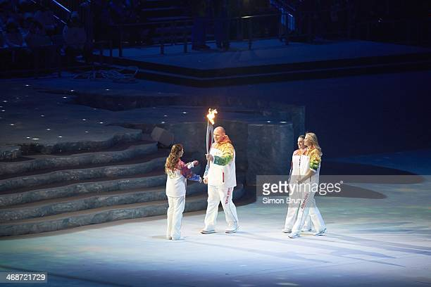 2014 Winter Olympics Russia Alexander Karelin handing over Olympic torch to Alina Kabaeva as Yelena Isinbaeva and Maria Sharapova watch during...